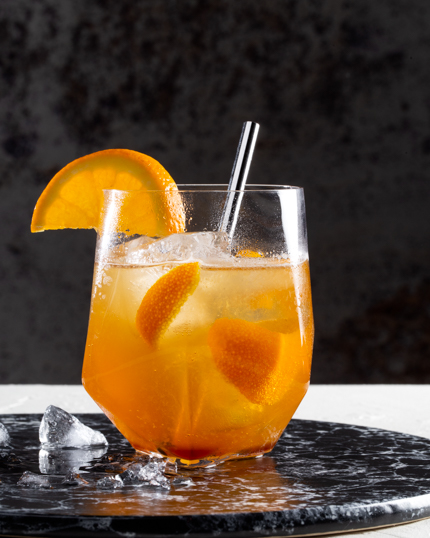 Glass of orange ginger cocktail made with dark brown sugar
