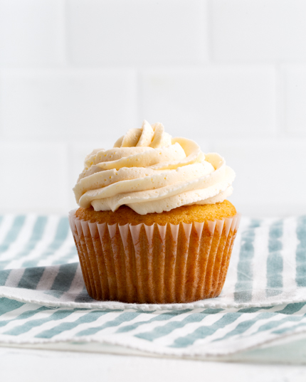 A vanilla cupcake topped with buttercream icing on a striped tea towel