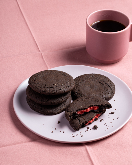 A plate of dark chocolate cookies stuffed with red marzipan shown with a cup of coffee