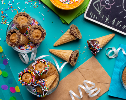 Chocolate dipped ice cream cones full of brown sugar fudge with rainbow sprinkles and party decor