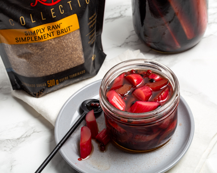 Mason jar of pickled rhubarb on a plate with a serving spoon and a package of Redpath Simply Raw Turbinado Sugar