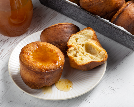 Two lemon spelt popovers on a plate, one cut in half, with lemon syrup on top and a pitcher of lemon syrup behind