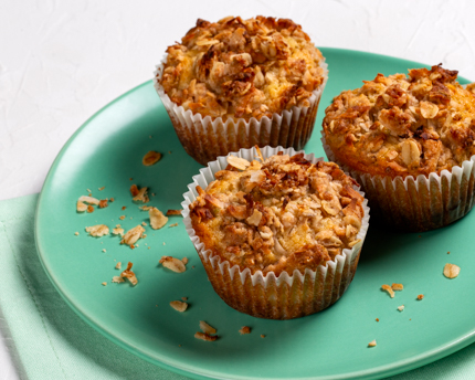 Three muffins topped with coconut streusel on a green plate