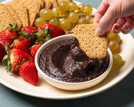 Bowl of chocolate hummus on a platter with graham crackers, figs, strawberries, and grapes