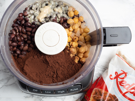 Food processor full of beans, chickpeas, instant espresso and sugar syrup on a marble counter with a package of Redpath Dark Brown Sugar