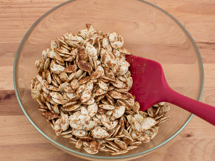 Stirring dry pumpkin seeds with sugar and spices in a glass bowl with a spatula