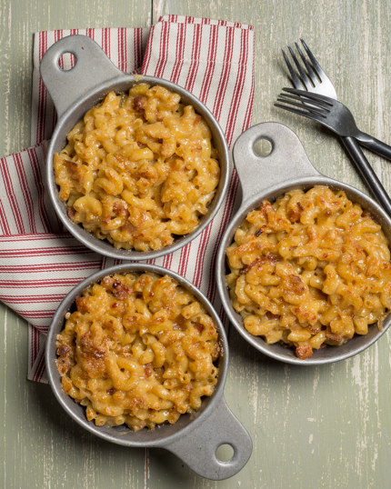 Three bowls of macaroni and cheese, with napkins and forks