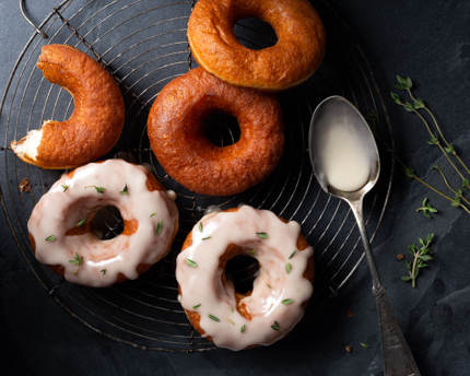 Five yeasted doughnuts on a cooling rack, two iced and sprinkled with thyme, with a spoon and thyme sprigs