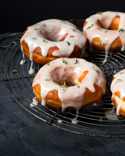 Yeast donuts on a cooling rack, coated with thyme sugar glaze
