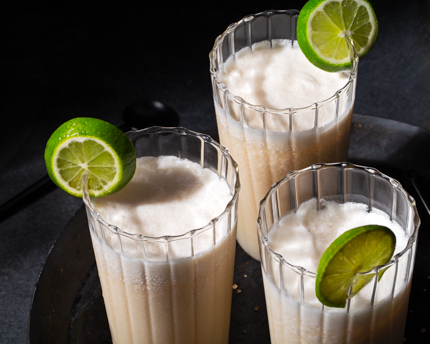 Three glasses of coconut kombucha garnished with lime slices on a black plate