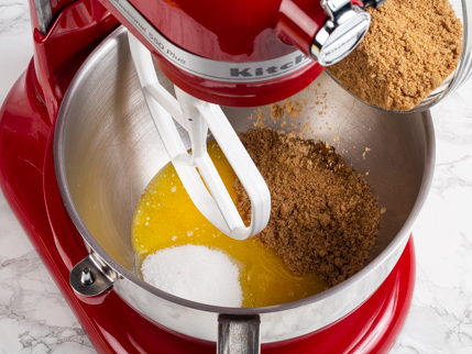 Adding brown sugar to a mixing bowl of melted butter and granulated sugar