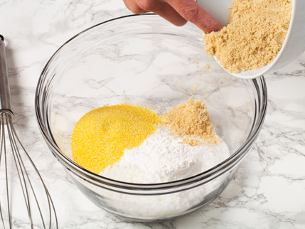 Adding golden yellow sugar to a glass mixing bowl of flour and cornmeal
