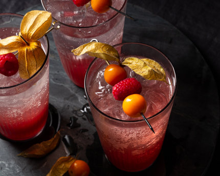 Three glasses of raspberry gooseberry shrub mixed with soda and garnished with raspberries and gooseberrries