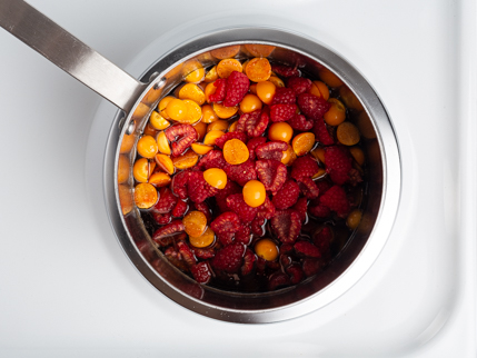 Halved raspberries and gooseberries in a pot of simple syrup