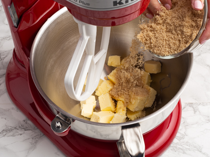Adding golden sugar to cubes of butter in a stand mixer bowl