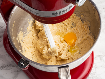 An egg cracked into creamed golden sugar and butter in a stand mixer bowl