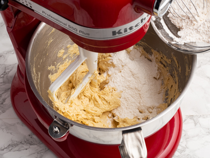 Adding dry ingredients from a bowl to creamed golden sugar, butter, and eggs in a stand mixer bowl
