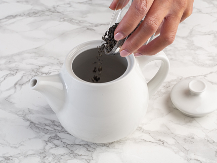 Pouring green tea leaves from a glass bowl into a white teapot