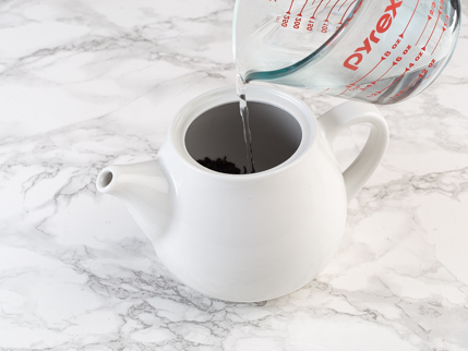 Pouring boiling water from a glass measuring cup into a teapot of tea leaves and tea spirit