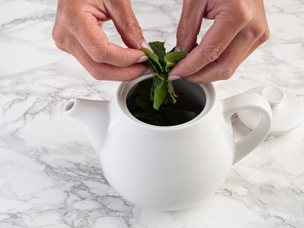 Tearing mint leaves and putting them in a teapot