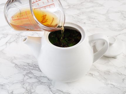 Pouring tea spirit from a glass measuring cup into a pot of mint tea