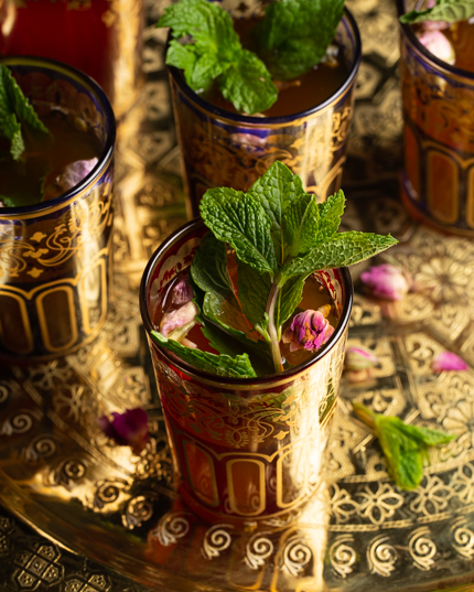 Five colourful glasses of Moroccan mint tea garnished with mint leaves on a gold platter