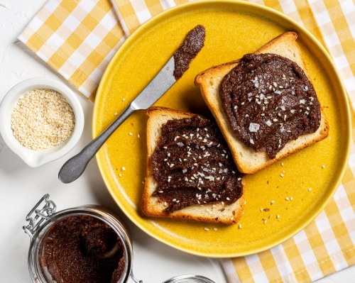 Cocoa tahini spread on two slices of toast, on a yellow plate with a knife