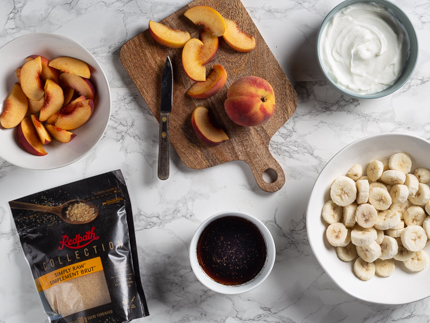 Slices of peach and bananas in bowls, a sliced peach on a cutting board, a bowl of yogurt, a cup of tea, and a bag of Redpath Simply Raw™ Turbinado Sugar