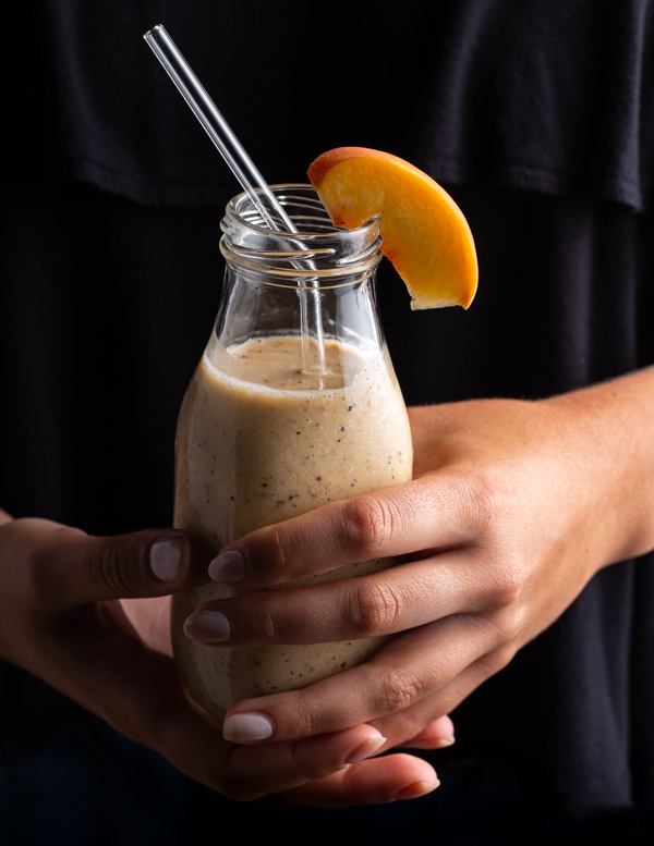 A woman's hands holding a single-serving bottle of banana peach Earl Grey smoothie with a glass straw, garnished with a slice of peach