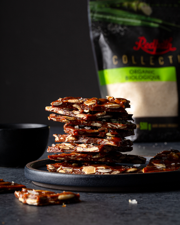 A stack of broken pieces of pumpkin seed brittle on a dark background and a bag of Redpath Collection Organic Granulated Sugar