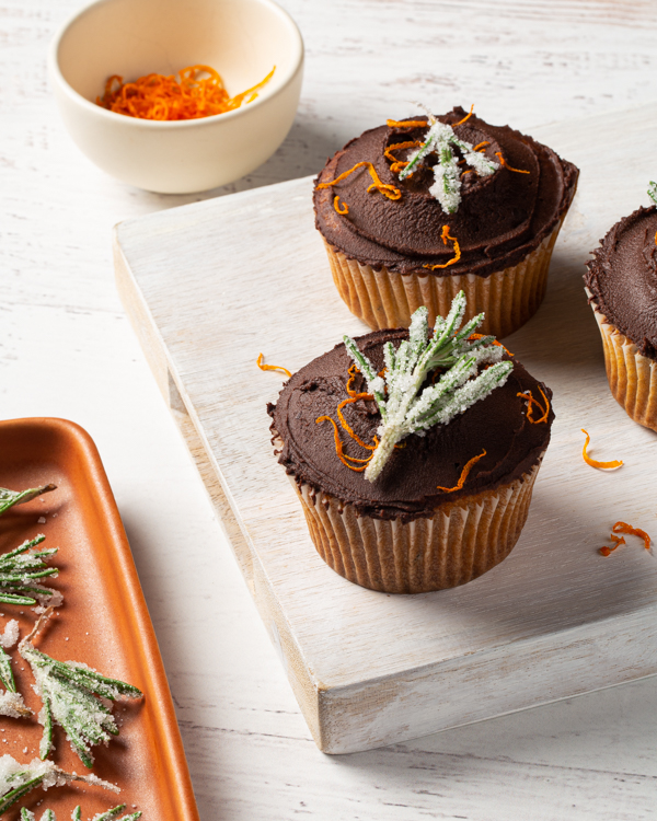 Three cupcakes topped with chocolate ganache, orange zest and sugared rosemary on a whitewashed board with extra toppings