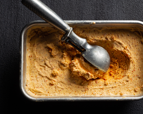 Carrot ice cream in a metal tin with an ice cream scoop