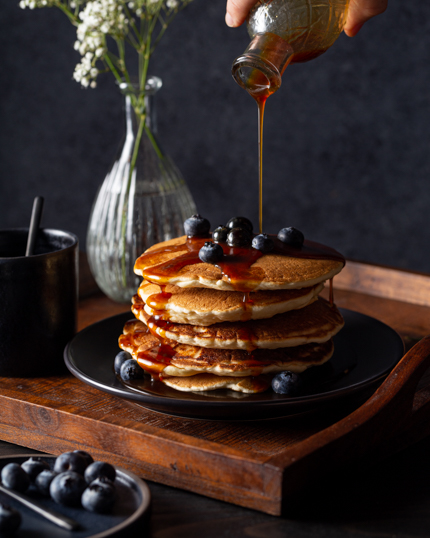 Pouring molasses pancake syrup from a bottle onto a stack of pancakes with blueberries