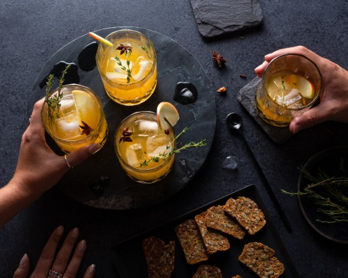 Hands reaching for glasses of Pumpkin Spice rum cocktail, served with crackers