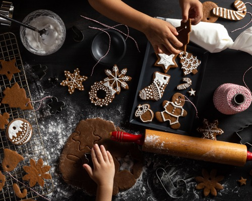 An assortment of gingerbread cut-out cookies on a cooling rack, counter, and pan with icing and decorating equipment