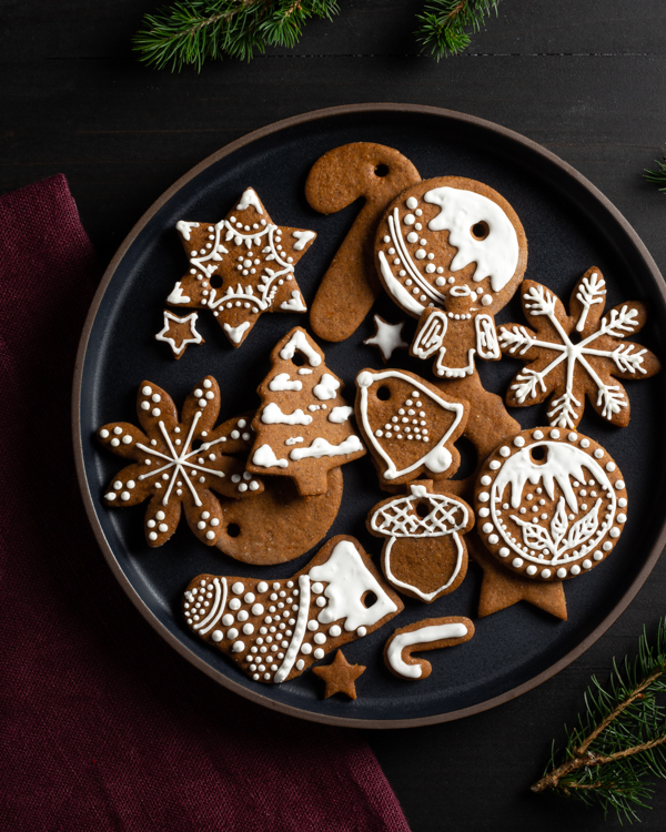 A circular dish full of gingerbread cut-out cookies decorated for Christmas