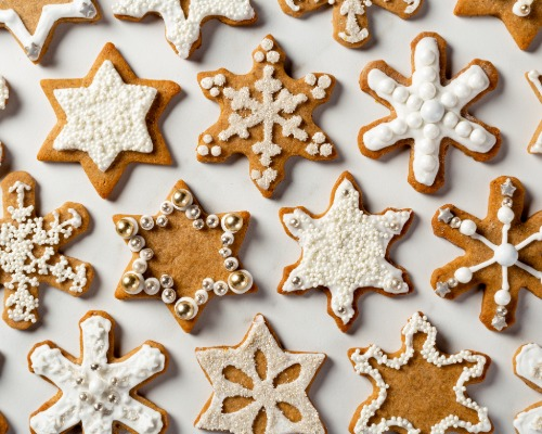 Gingerbread spiced sugar cookies shaped like stars and snowflakes with royal icing and sprinkles