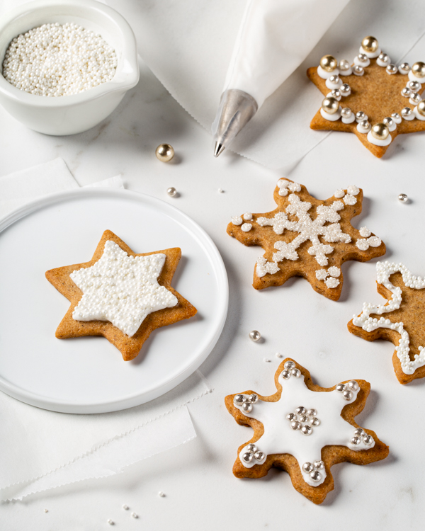 Gingerbread spiced sugar cookies decorated with royal icing, with a piping bag and a bowl of sprinkles