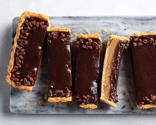 Slices of chocolate chestnut ganache tart on a marble cutting board
