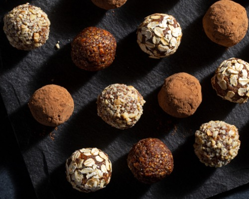 An assortment of fig breakfast bites rolled in nuts and cocoa powder