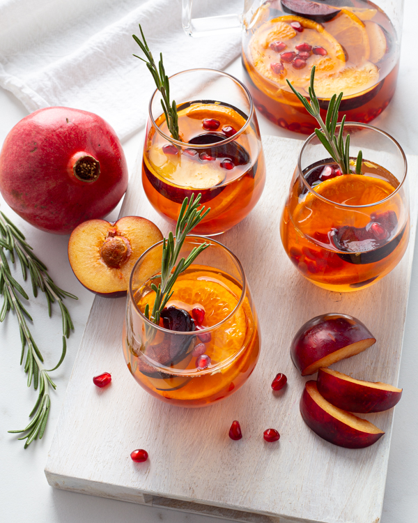 Three glasses of white sangria over ice garnished with rosemary sprigs and sliced fruit with a pomegranate