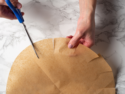 Cutting a parchment round with scissors to fit a cake pan