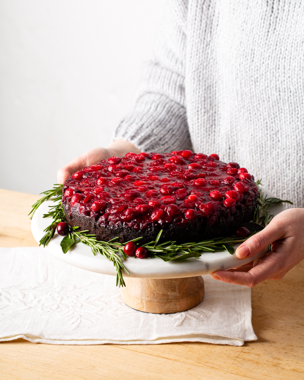 Cranberry chocolate upside-down cake on a cake stand garnished with rosemary and cranberries.