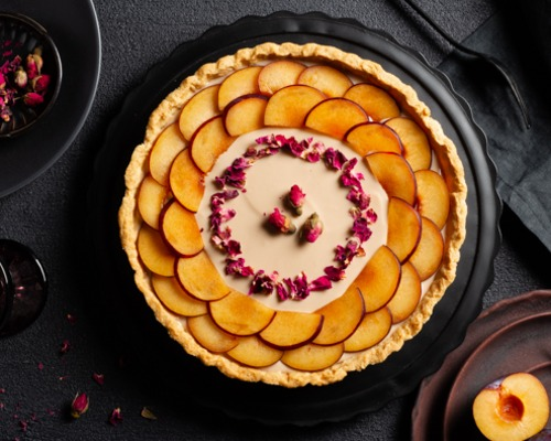Plum custard tart decorated with sliced plums and dried rose petals on a black platter on a black table