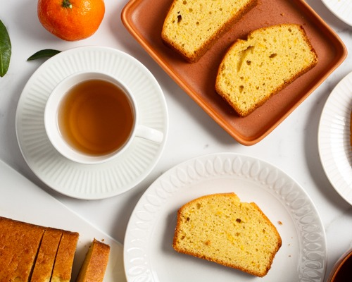 Slices of orange pound cake on plates with a cup of tea and an orange