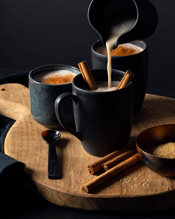 Pouring hot horchata from a pitcher into a mug with cinnamon sticks
