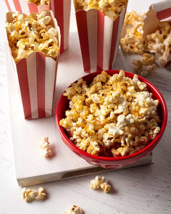 Kettle corn in a red bowl and red and white striped popcorn bag