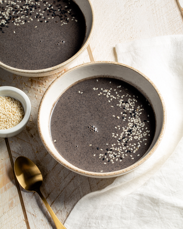 Two bowls of black sesame seed soup garnished with white and black sesame seeds on a wooden table