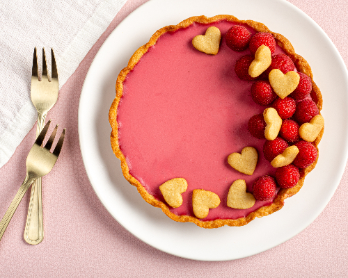Raspberry rosewater panna cotta tart decorated with raspberries and heart-shaped cookies with 2 golden forks