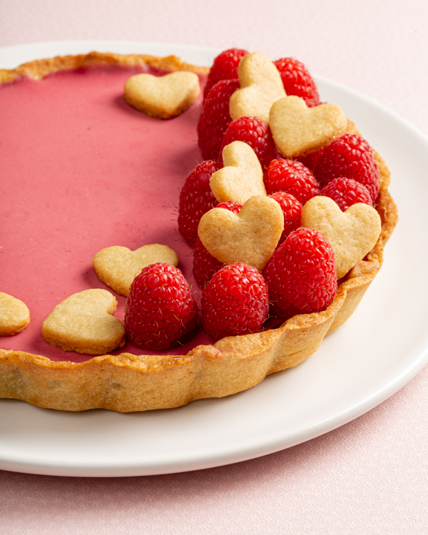Raspberry rosewater panna cotta tart decorated with raspberries and heart-shaped cookies